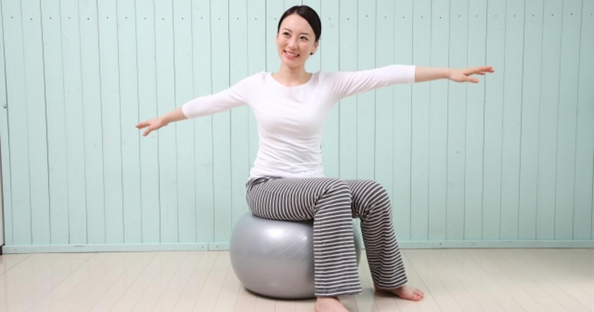 バランスボールに乗って体を捻る女性