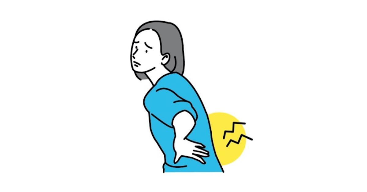 腰に手を当て、腰痛に悩む女性
