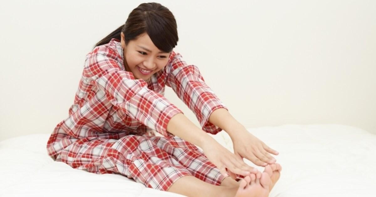 寝る前に腰痛改善のストレッチをしている女性