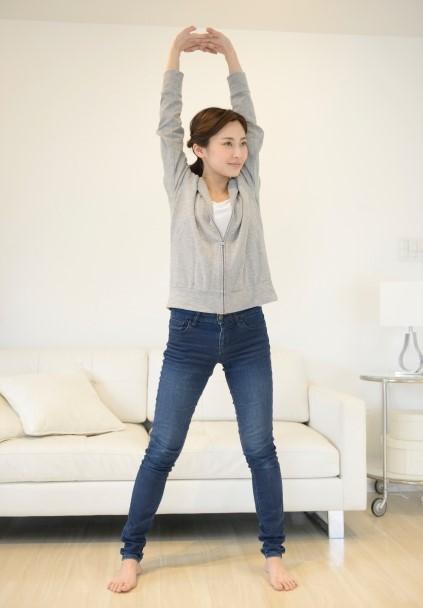 背伸びをしてお腹の力を意識している女性